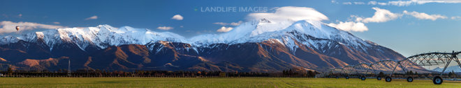 Mount Hutt in winter with farming center pivot in foreground and hot air balloon in sky, Canterbury, New Zealand