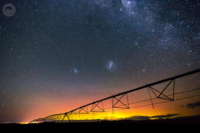 Center pivot irrigator silhouetted by the Aurora Australis, Mid-Canterbury, New Zealand, landscape