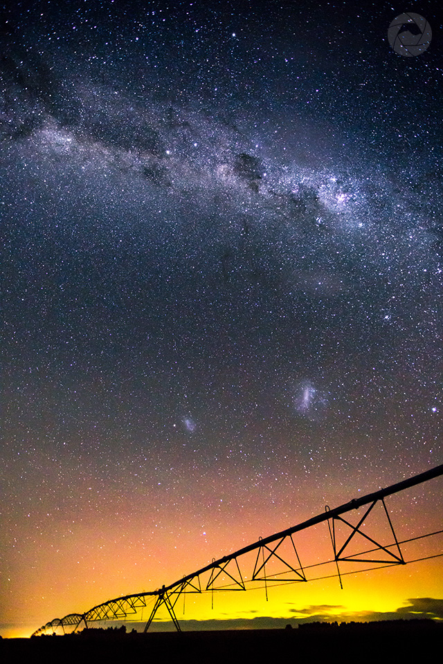 Center pivot irrigator silhouetted by the Aurora Australis, Mid-Canterbury, New Zealand, portrait