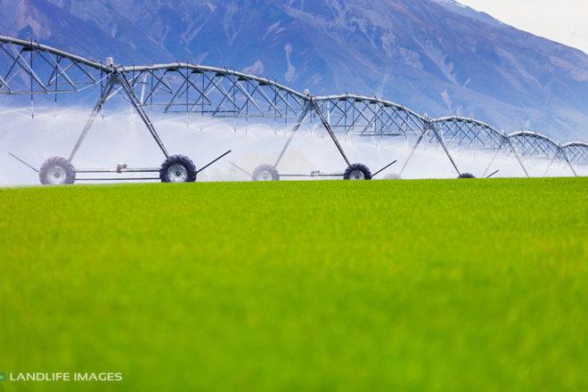 Centre pivot irrigator watering grass, Methven, New Zealand