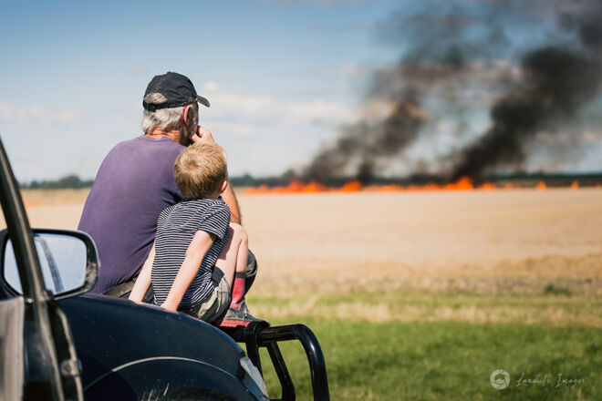 Grandad and grandson watching the controlled burnoff, Methven, Canterbury, New Zealand